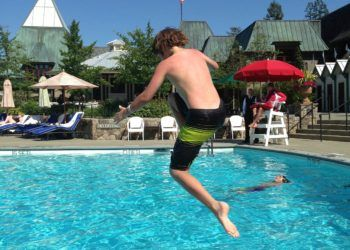 Boy jumping into pool during Summer